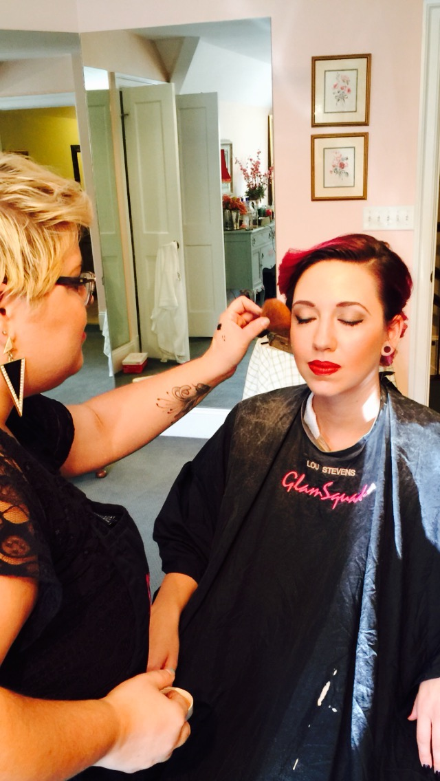 Malory applying blush on a bridesmaid